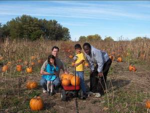 Abubakar picks pumpkins with his host family during his first visit to Iowa through IRIS's YES Program