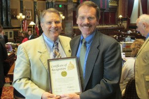 Del Christensen (right), Executive Director for Iowa Resource for International Service (IRIS), accepts the Iowa Senate certificate of recognition, which is presented by Senator Daryl Beall (left).