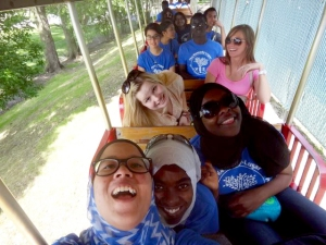 Program Assistant Brittany Haga, former Public Relations intern Kelsey Hartnett, and the YES students pose for a goofy group photo on a train ride.